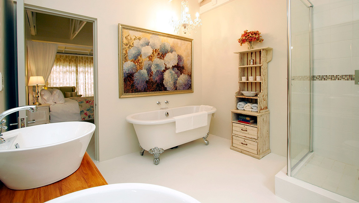 En suite master bathroom with twin basins, ball and claw bath and crystal chandelier
